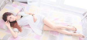 ベッドでリラックスする若い女性の姿